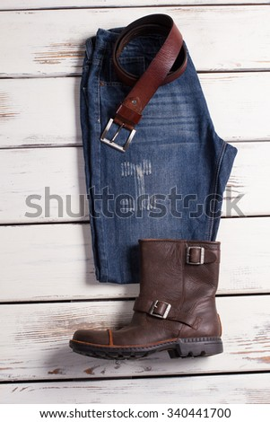 Casual wear of stylish man. Jeans, belt and boots on a wooden background. - stock photo