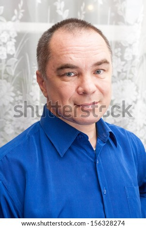 casual weared mid age man indoors, looking at camera - stock photo