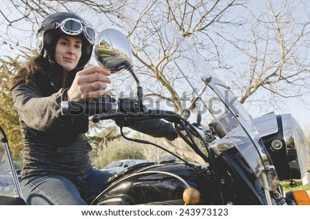 Casual woman at motorcycle with adjusting mirror