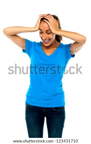 Casual woman expresses her silly mistake by holding her head. She is amazed - stock photo