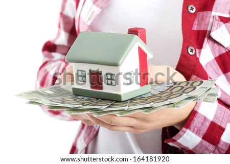 Casual woman holding money and house on hand. Over white.  - stock photo