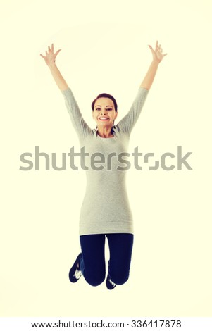 Casual woman jumping in air. Vertical