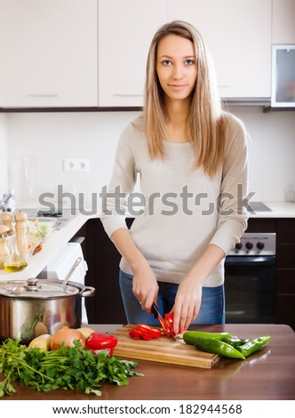 Casual  woman slicing  pepper on table at domestic kitchen