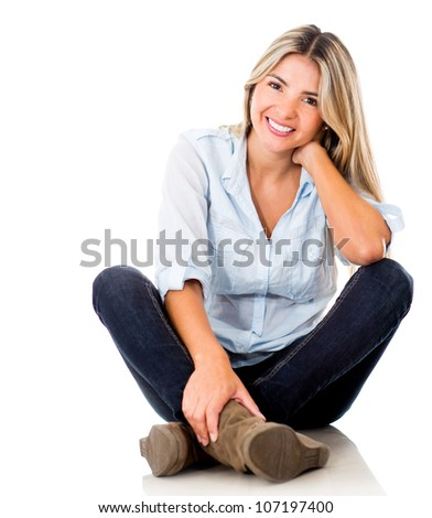 Casual woman smiling sitting on the floor - isolated over a white background - stock photo