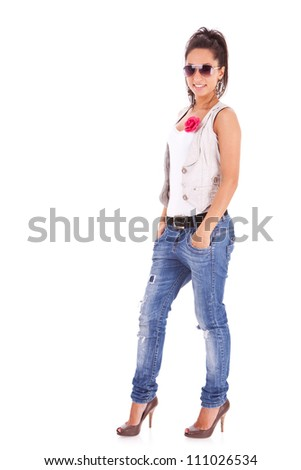 casual woman standing with her hands in her pockets and smiling isolated over a white background