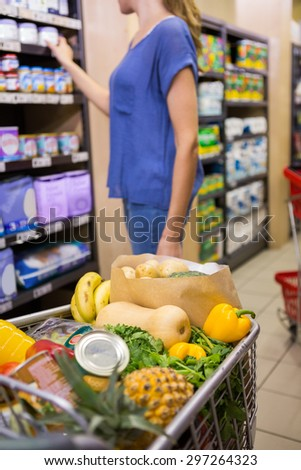 Casual woman taking product on shelf at supermarket