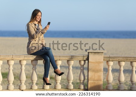 Casual woman texting in a smart phone on the beach in winter with the sea in the background - stock photo