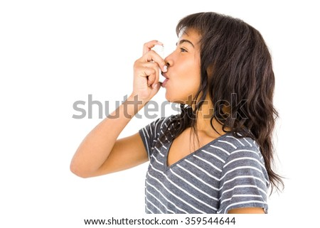 Casual woman using her inhaler against white background - stock photo