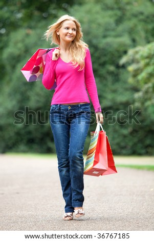 Casual woman with shopping bags walking outdoors - stock photo
