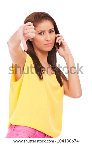 casual woman with thumb down gesture speaking on mobile phone - stock photo