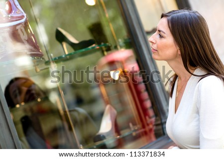 Casual woman wondow shopping and looking at shoes - stock photo