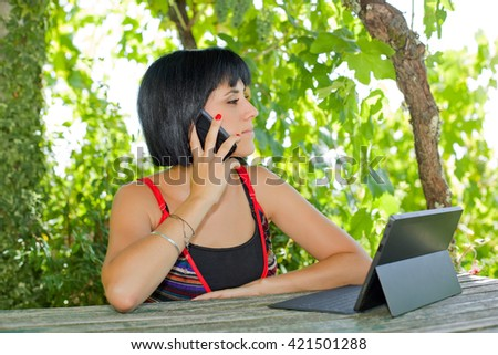 casual woman working with a tablet, outdoor - stock photo