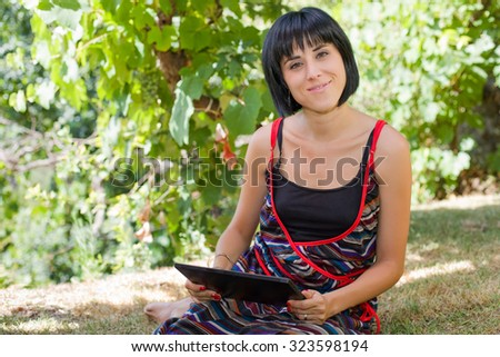 casual woman working with a tablet pc, outdoor - stock photo