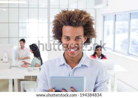 Casual worker using tablet pc in the office - stock photo
