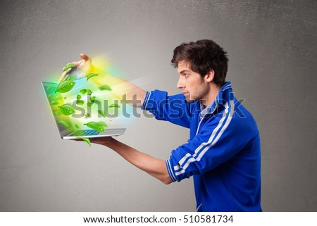 Casual young boy holding laptop with recycle and environmental symbols