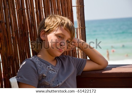 Casual young boy on balcony with sea view behind . - stock photo
