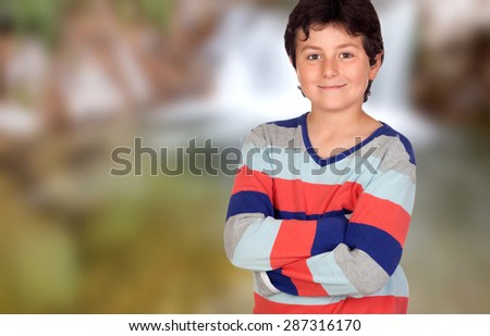 Casual young boy with arms crossed on a unfocused background - stock photo