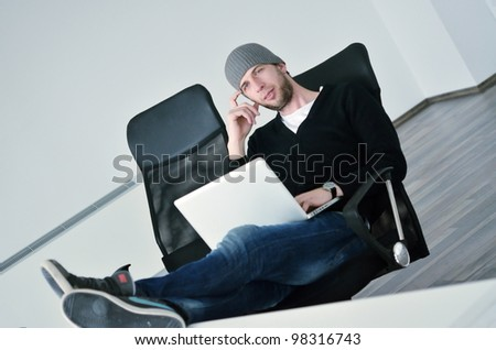 casual young business man relax and work on laptop computer with foots on table
