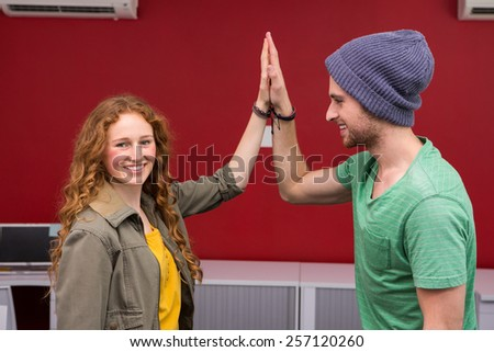 Casual young businessman and woman high fiving in office - stock photo