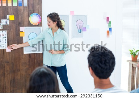 Casual young businessman giving presentation to colleagues in office - stock photo