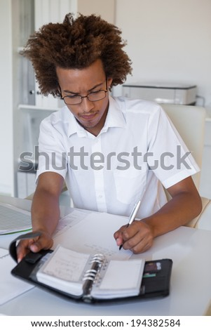 Casual young businessman organizing his schedule at his desk in his office - stock photo
