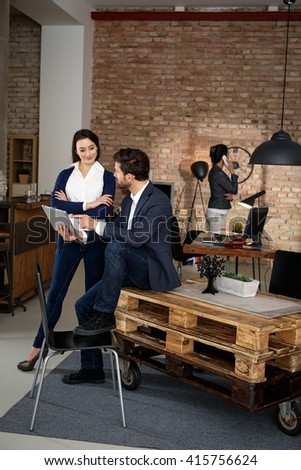 Casual young businesspeople working in startup office, using tablet computer.