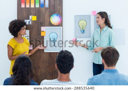Casual young businesswoman giving presentation to colleagues in office - stock photo