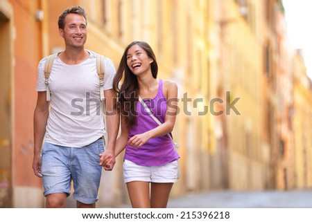 Casual young couple holding hands walking in Rome, Italy, Europe. Multiracial couple in love having fun laughing together. Asian woman, Caucasian man. - stock photo