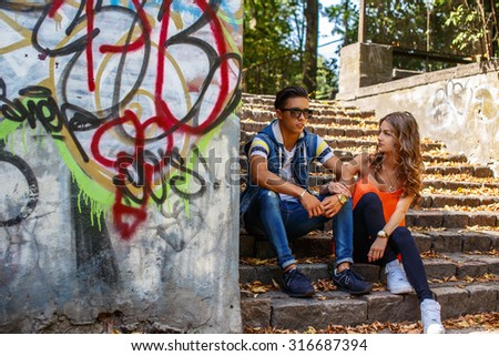 Casual young couple sitting on stairs. - stock photo