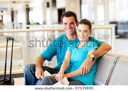 casual young couple waiting for flight at airport