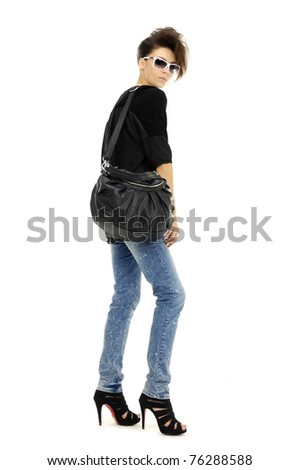 casual young fashion mode in sunglasses and jeans show in studio - stock photo