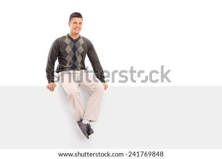 Casual young guy sitting on a blank signboard isolated on white background