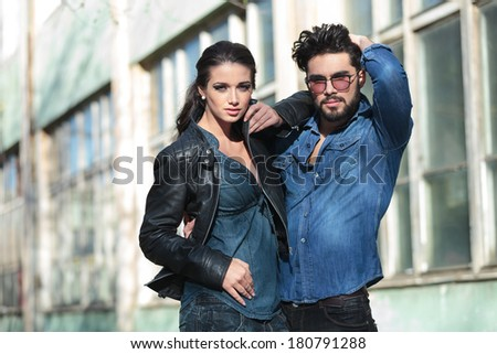 casual young man and woman posing outdoors, embraced and looking into the camera. she is holding her elbow on his shoulder while he is passing his hand through his hair - stock photo