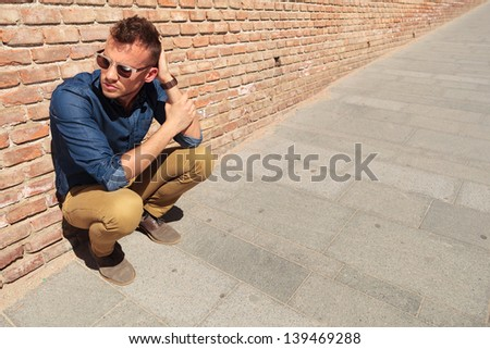 casual young man crouching by a brick wall and holding a hand with the other which is on the back of his head while looking away from the camera