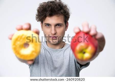 Casual young man holding apple and donut - stock photo