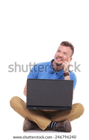 casual young man holding his laptop while sitting on the floor with his feet crossed and looking away in a pensive manner. on a white background - stock photo