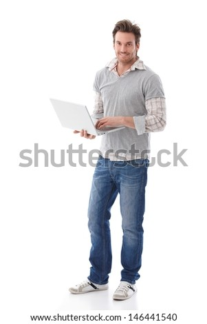 Casual young man holding laptop in hands, smiling. - stock photo