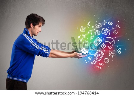Casual young man holding laptop with colorful hand drawn multimedia symbols - stock photo