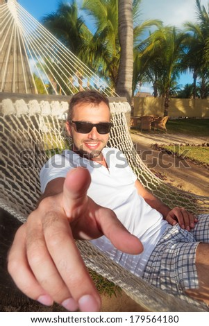 casual young man in a hammock in a resort pointing his finger to the camera - stock photo