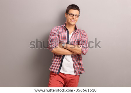 Casual young man in a red checkered shirt posing and leaning against a gray wall