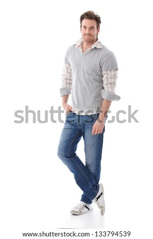 Casual young man in jeans and shirt smiling.