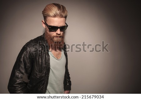 Casual young man in leather jacket pulling his sunglasses, sitting on the floor, looking at the camera