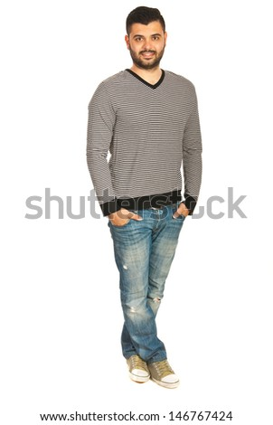 Casual young man in striped shirt and jeans standing with legs crossed isolated on white background