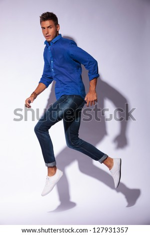 casual young man jumping in a walking position and looking at the camera, on light background with shadow