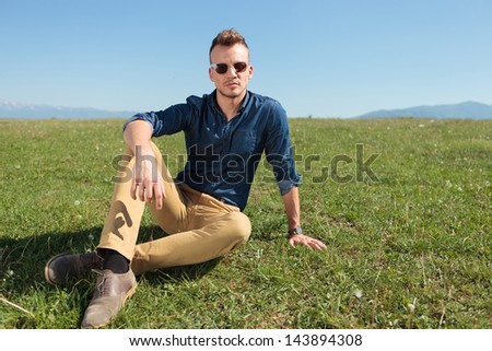 casual young man laying on the ground and looking at the camera
