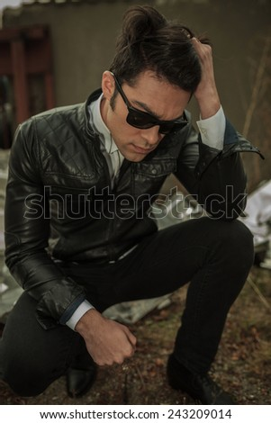 Casual young man looking down while sitting, fixing his hair.