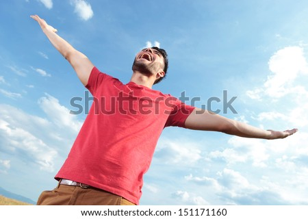 casual young man outdoor shouting at the sky while holding his hands wide open