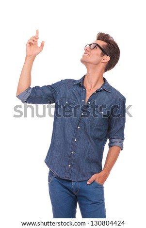 casual young man pointing and looking upwards while holding a hand in his pocket and smiling. isolated on a white background - stock photo