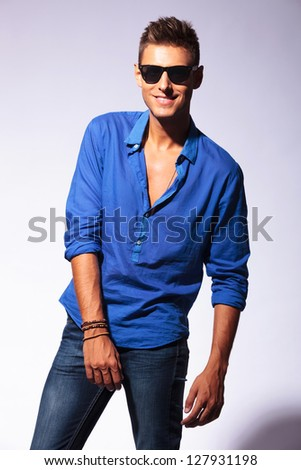 casual young man posing on a gray background with a cute smile on his face