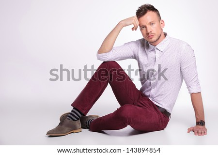 casual young man posing on the floor with his hand at his temple and elbow on knee while looking at the camera. on gray background - stock photo